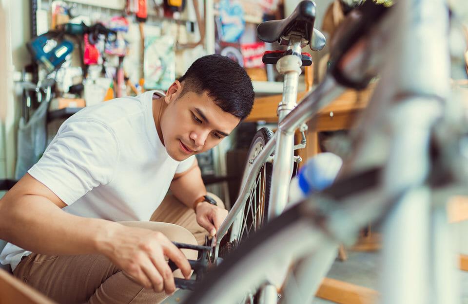 Man fixing bike in workshop.