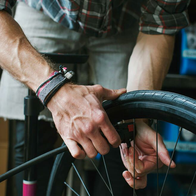 Close up of man fixing a bike tyre.