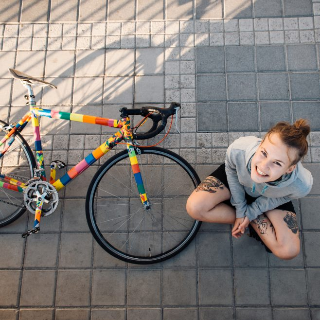 Happy young woman sitting near bicycle in the morning city at sunrise